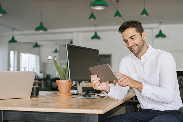 man looking pleasantly at tablet